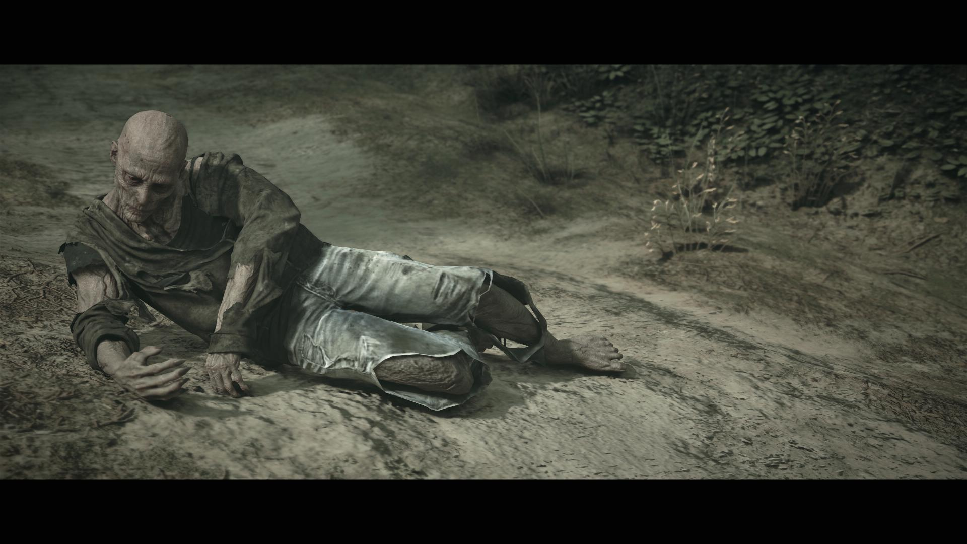 An almost sepia shot of a zombie, its clothes torn, lying on a dirt path