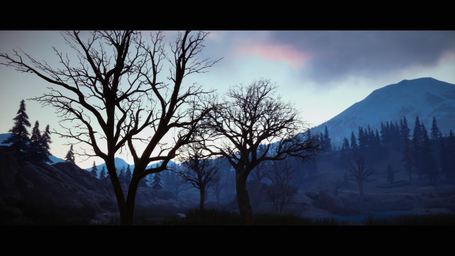 The early morning sky over a barren forest in the game Days Gone.