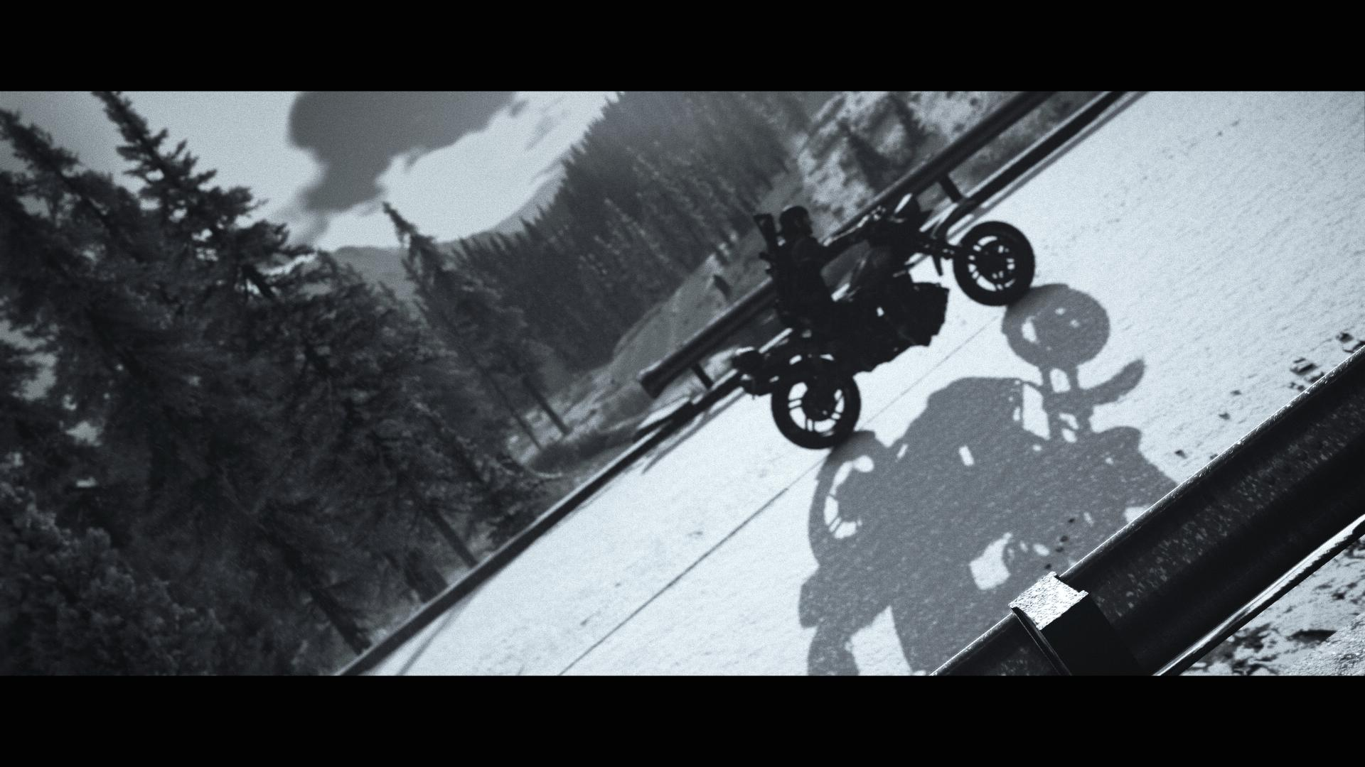A black and white screenshot of Days Gone. A silhouetted player character rides a motorbike across a bridge, in the depths of a forest.