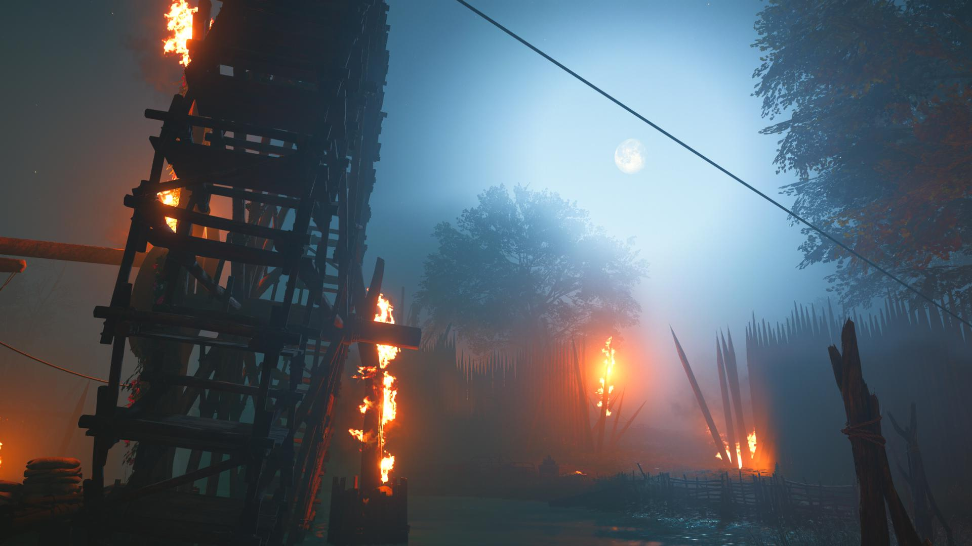 A wooden water wheel, in the fog, on fire.