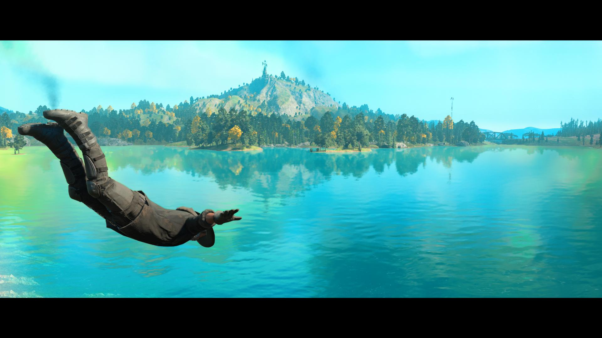 The player dives into a lake. In the distance, a forest and mountain.