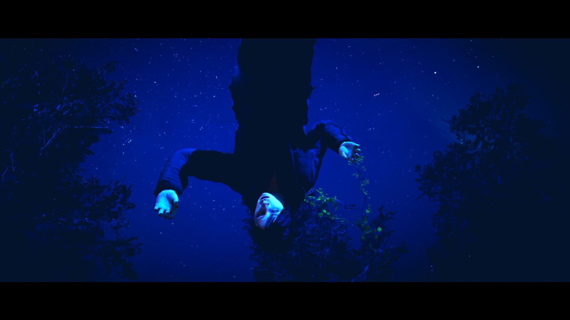It's a videogame screenshot of a body floating in a lake, taken from underneath the water, at night.