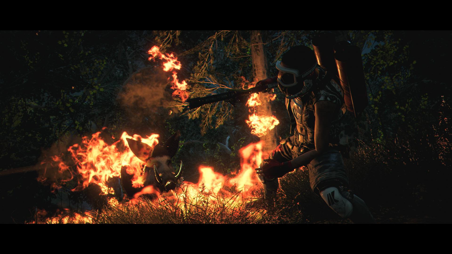 A man with a motorcycle helmet on, welding a flamethrower in the woods at night. The area surrounding them is on fire.