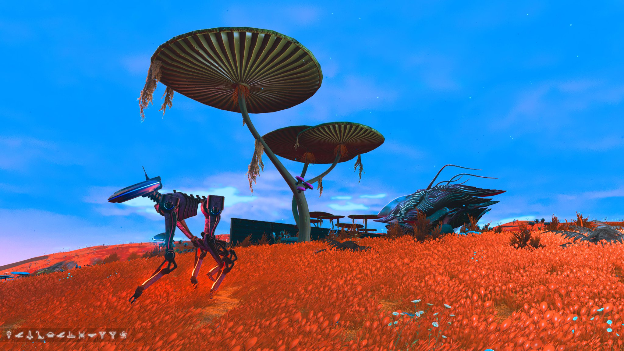 A blue sky, orange grass - a mysterious organic ship sits barely in view, a metallic dog like robot walks past.