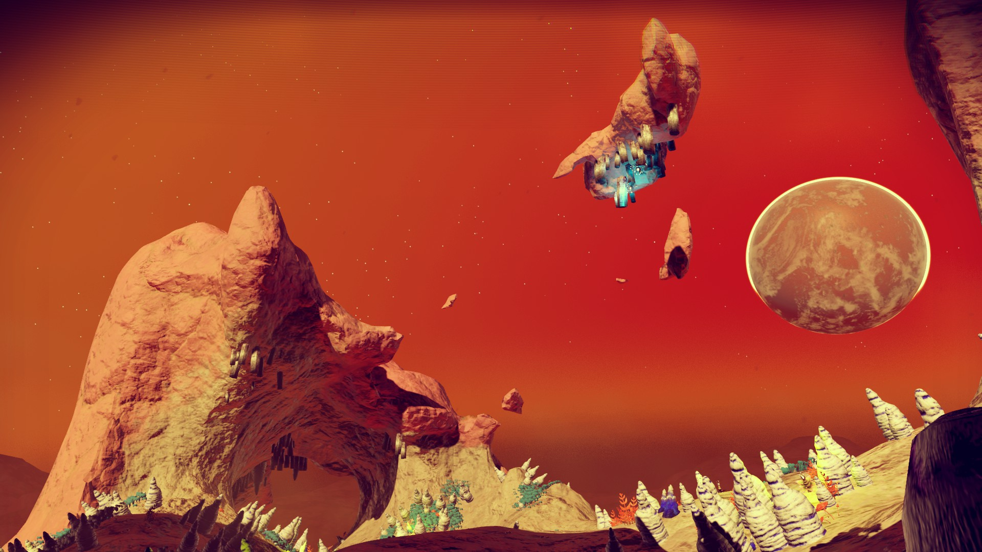 An alien looking landscape from No Man's Sky. A rocky outcrop, a rock floats in an orange and red sky, a planet is visible in the sky.