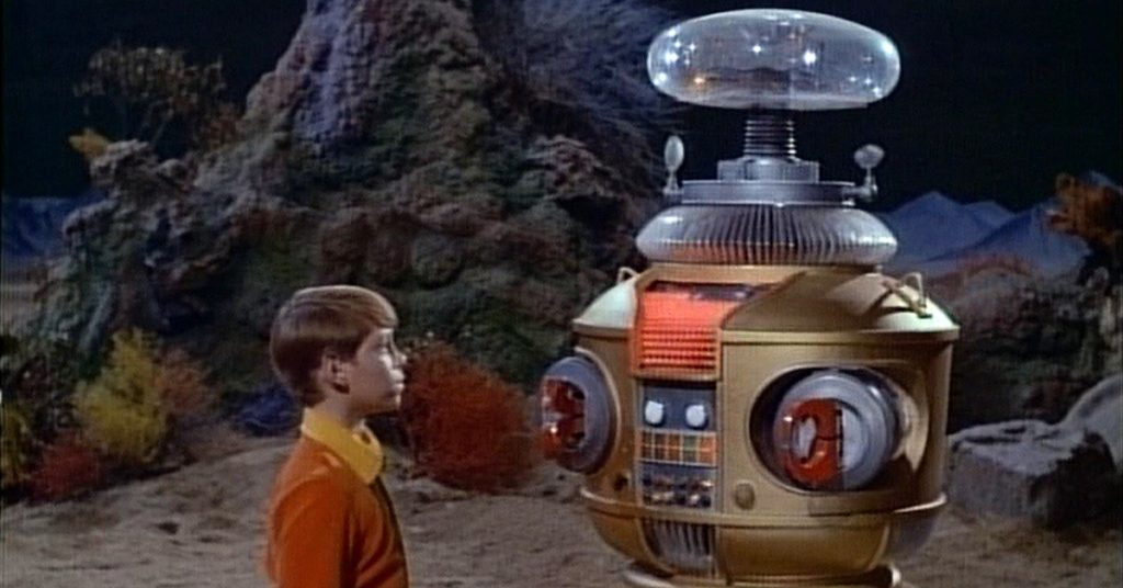It's the robot from the original Lost In Space conversing with a kid whilst on an alien planet.